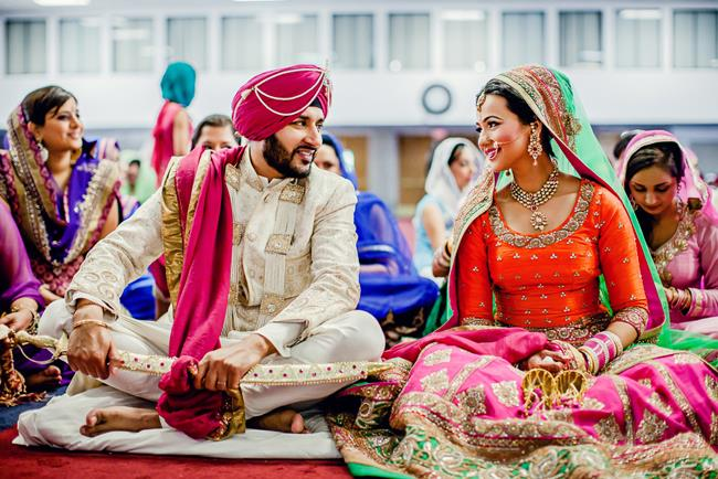 Indian-bride-and-groom-talking-smiling-during-Sikh-wedding1