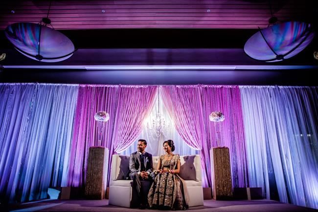 Indian reception stage with purple and blue lighting and lounge sofa