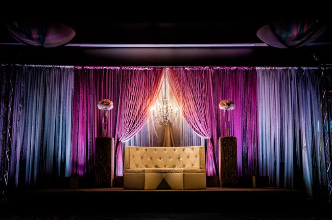 Indian reception stage with white sofa and pink and blue uplighting